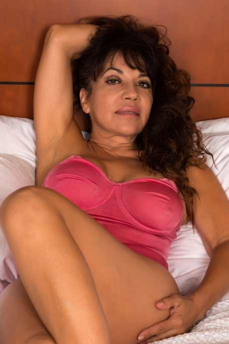 Reife dunkelhaarige Frau verführerisch auf dem Bett