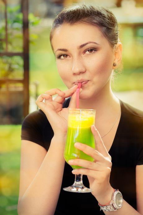 Junge Frau trinkt einen Cocktail