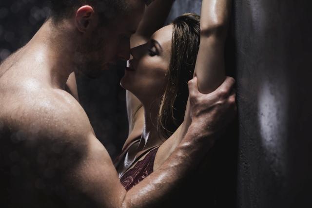 Pärchen lehnt an der Wand beim Küssen