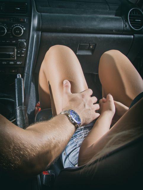 Mann legt einer Frau im Auto die Hand aus Bein