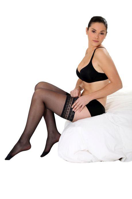 Dunkelhaarige reizvolle Frau in Unterschwäsche sitzend auf dem Bett