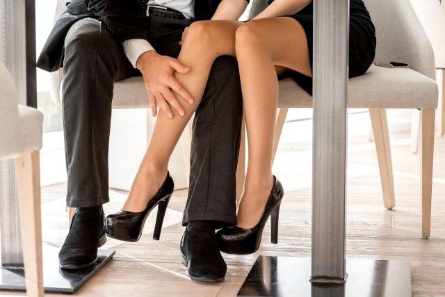 Mann streichelt Frauenbein unter Tisch