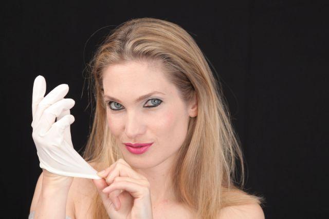 Blonde Frau mit Latexhandschuh