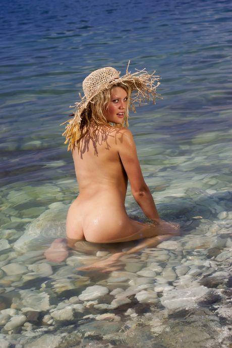 Nackte blonde Frau am Strand mit Hut
