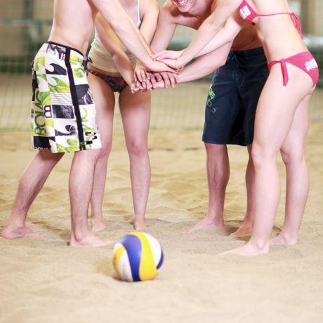 Gruppe junger Personen beim Beachvolleyball