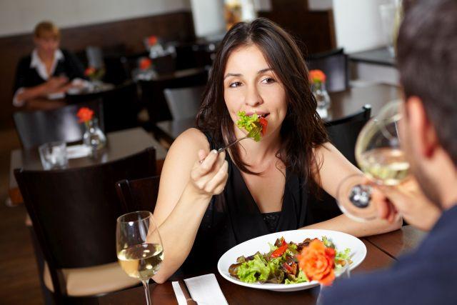 Frau sitzt im Restaurant und isst Salat