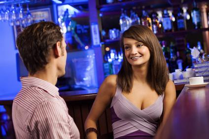 Mann spricht Frau in einer Bar an