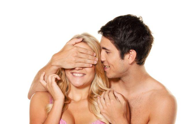 Mann steht hinter einer Frau und hält ihr die Augen zu