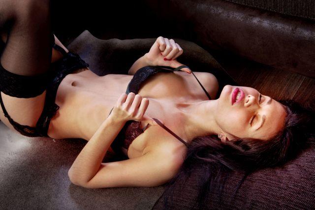 Dunkelhaarige Frau liegt in Dessous auf Bett