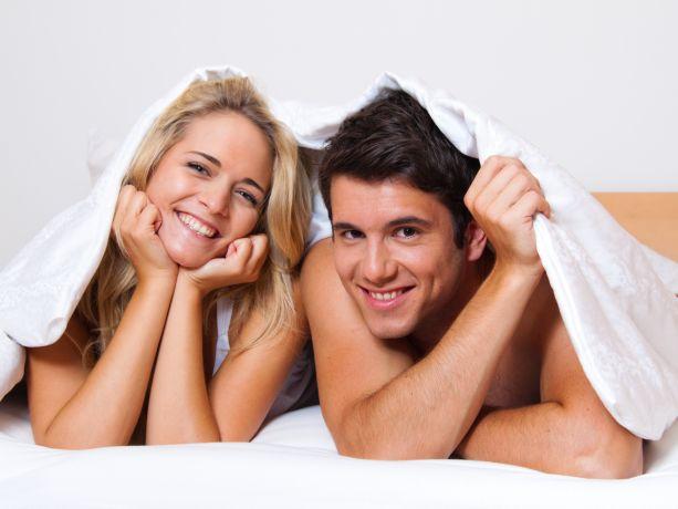 Paar liegt unter einer Decke im Bett