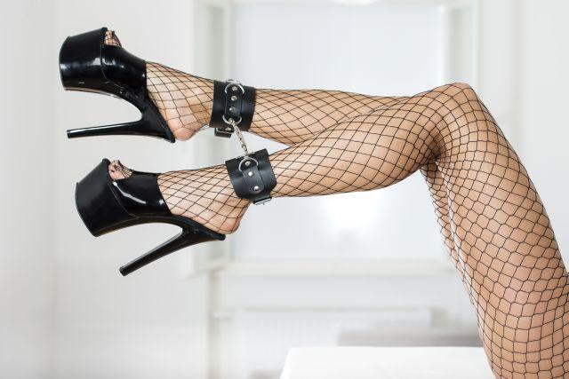 Beine einer an den Knöcheln gefesselten Frau in Highheels und Netzstrumpfhose
