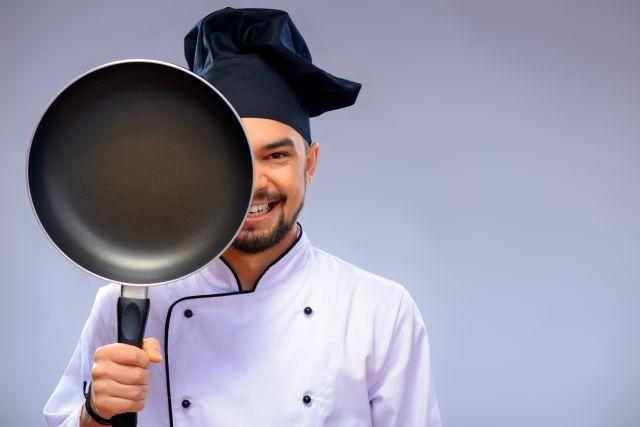 Koch mit Pfanne vor dem Gesicht
