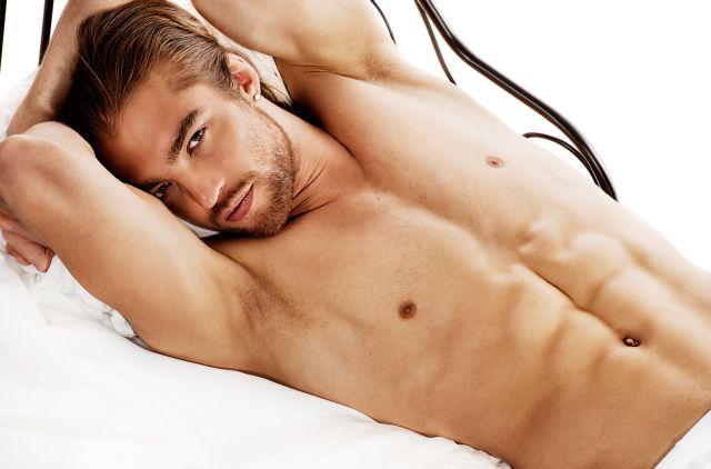 Muskulöser Mann liegt oberkörperfrei mit angewinkelten Armen auf einem weißen Bett.