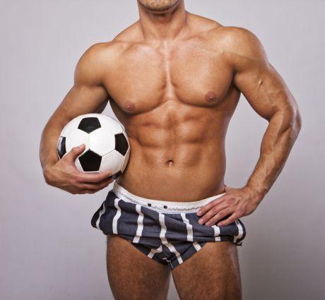 Muskulöser Mann in Boxershorts mit Fussball