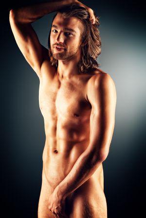 Junger nackter Mann mit langen Haaren bedeckt seinen Schritt.