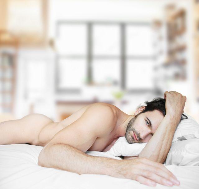 Nackter dunkelhaariger Mann liegt auf einem weißen Bett.