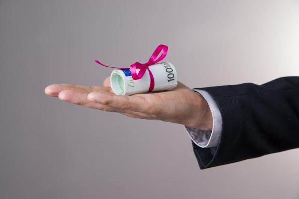 Männliche Hand präsentiert ein Bündel mit Geldscheinen