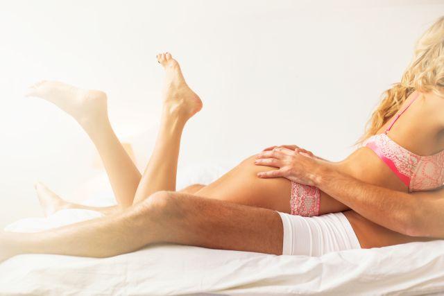 Frau liegt mit Unterwäsche auf einem Mann