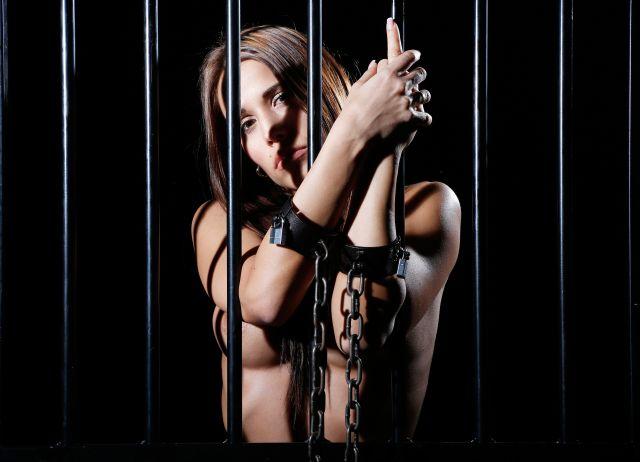 Leichtbekleidete Frau hinter Gitterstäben