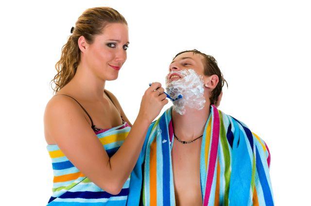 Frau rasiert Mann am Kinn