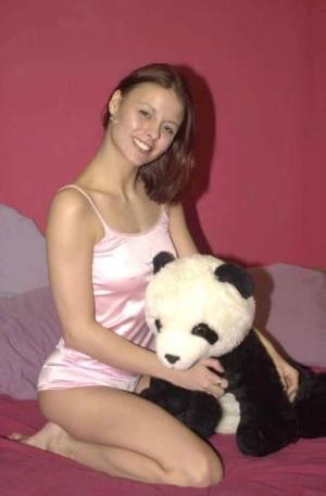 Junge Frau mit Panda-Plüschtier auf dem Bett