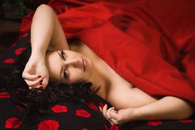 Dunkelhaarige Frau liegt zugedeckt mit roter Decke