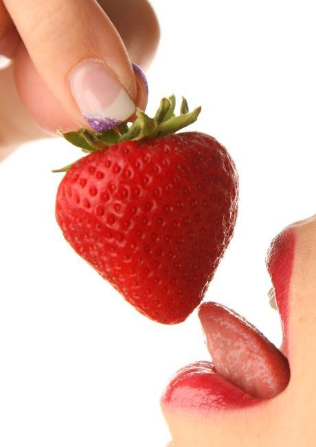 Frau vernascht Erdbeere