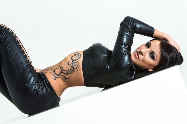 Tätowierte Frau liegt in schwarzer bauchfreier Latexkleidung auf dem Boden