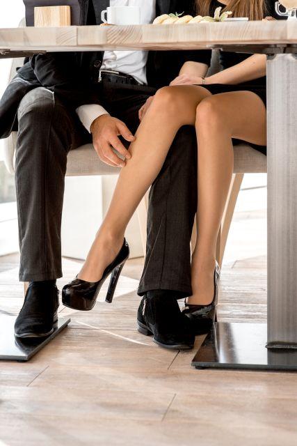 Paar kuschelt unter Restauranttisch
