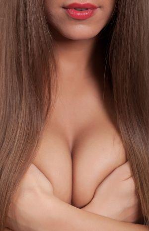 Frau bedeckt Brüste mit ihren Händen