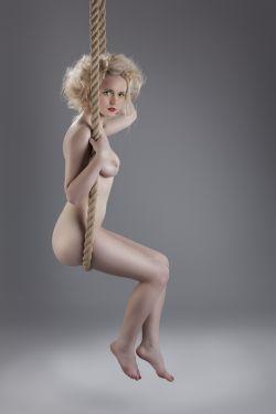 Nackte Frau schaukelt auf Seil...