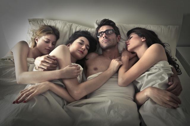 Mann liegt mit drei Frauen im Bett
