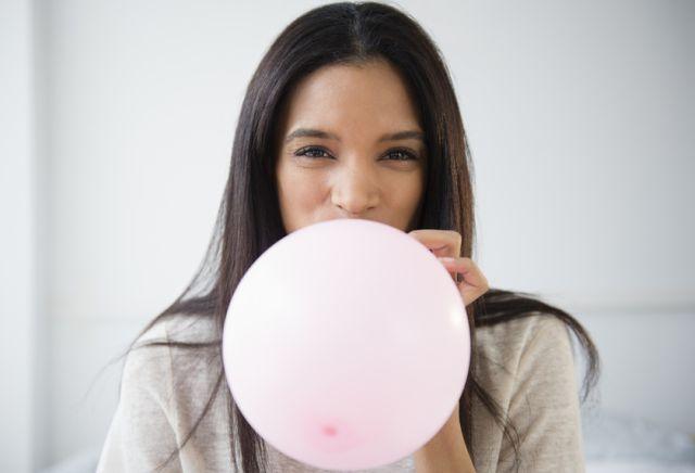 Frau bläst Luftballon auf