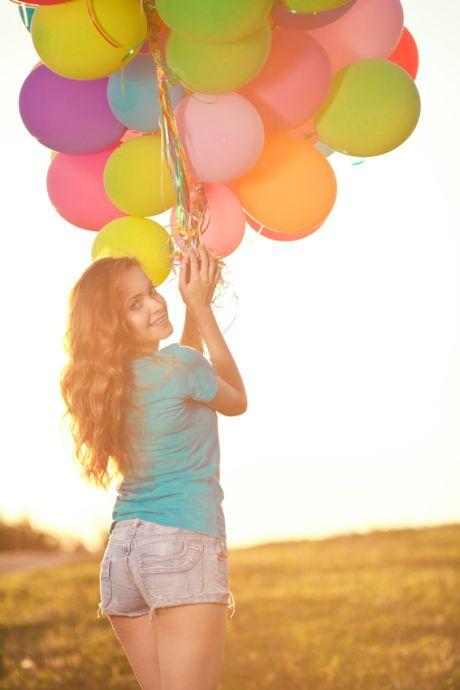 Frau hält zahlreiche bunte Luftballons