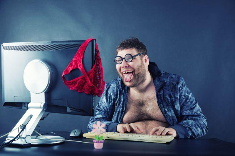Mann sitzt mit raushängender Zunge vor dem Computer auf dem ein roter Damenslip hängt