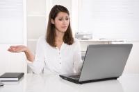Frau sitzt erstaunt vor Laptop
