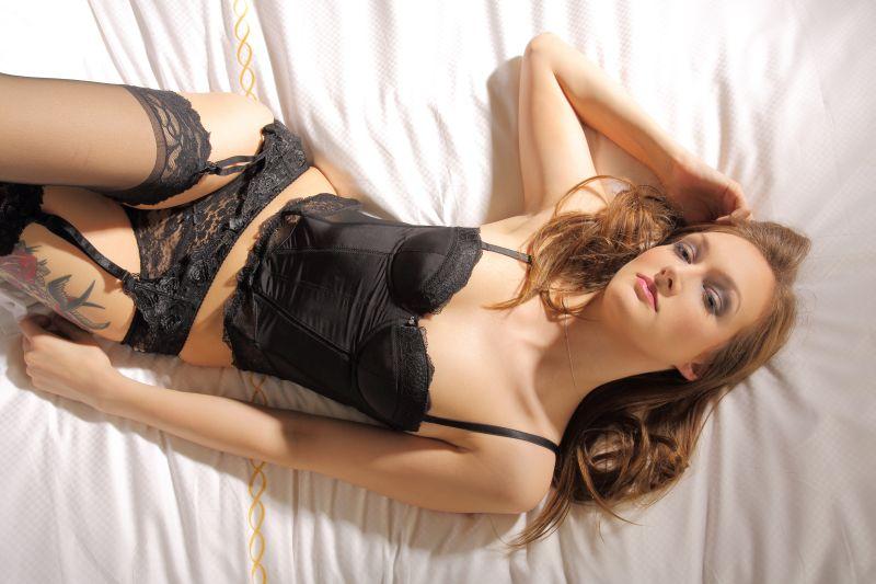 Attraktive Frau liegt in schwarzen Dessous auf weiem Bettlaken