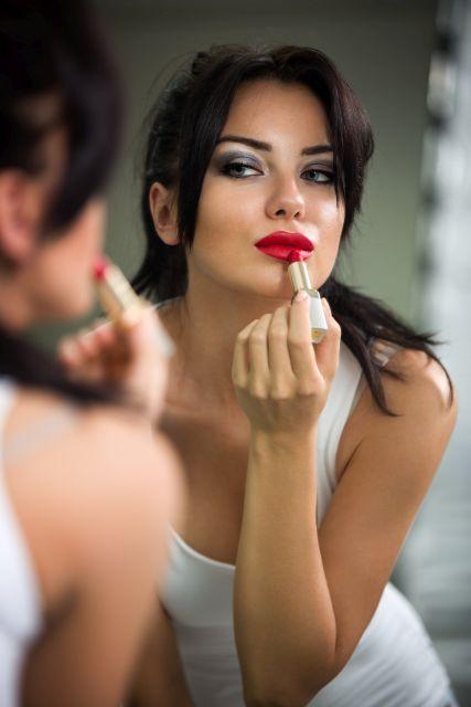 Frau schminkt sich vor Spiegel