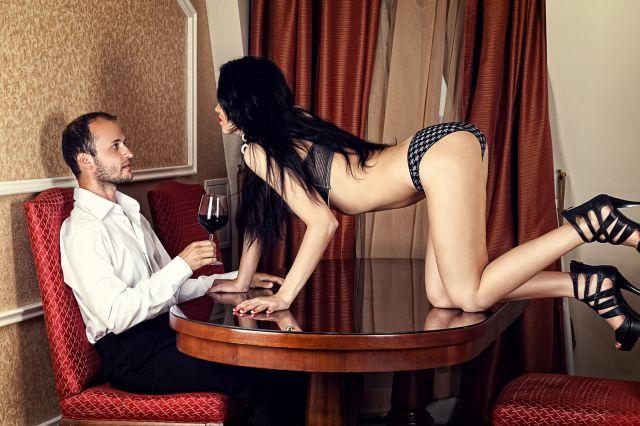 Frau in Dessous kniet auf Esstisch, an dem ein Mann mit Weinglas sitzt