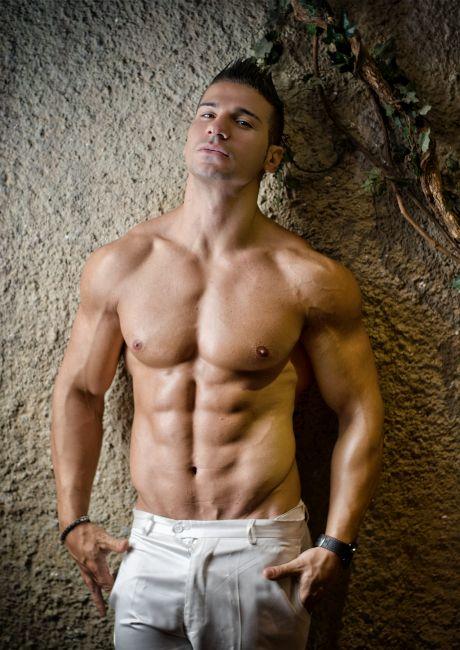 Attraktiver muskulöser Mann lehnt sich gegen eine Wand