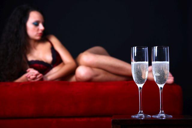 In Dessous bekleidete Frau auf dem Bett mit Champagner