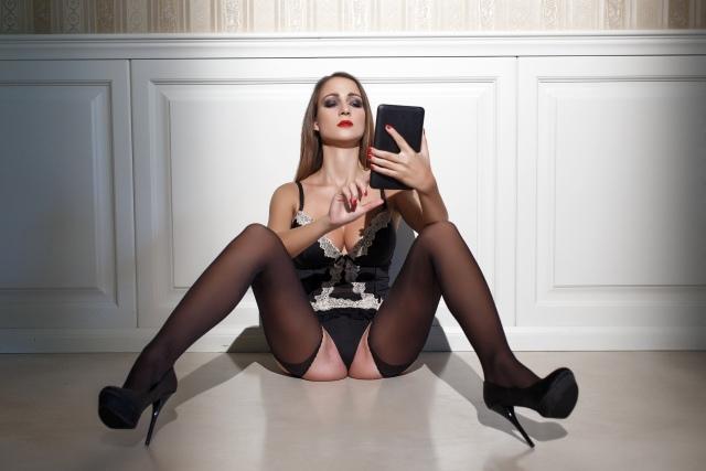 Sexy Frau sitzt auf Boden mit Smartphone in der Hand