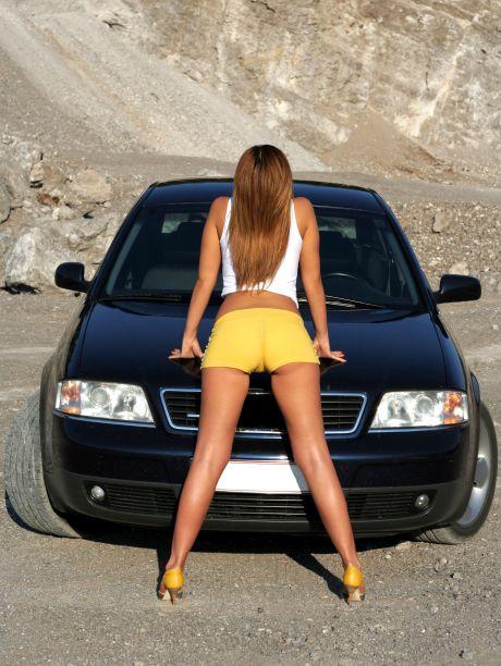 Sexy Frau lehnt sich an ein Auto