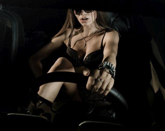 Sehr sexy gekleidete Frau sitzt am Lenkrad eines Autos