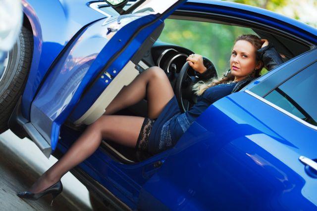 Sexy gekleidete Frau sitzt am Steuer eines Autos