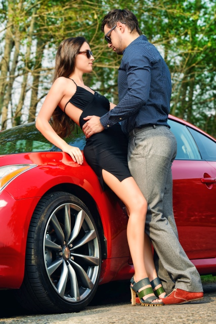 Pärchen in steht eng bei einander vor einem Auto