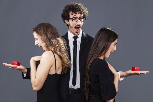 Mann bietet zwei Frauen jeweils ein Geschenk an