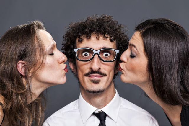 Mann wird von zwei Frauen links und rechts auf die Wange geküsst