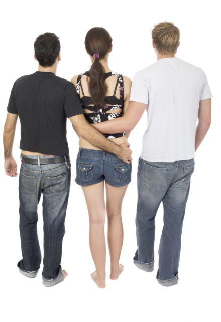 Frau in der Mitte wird von zwei Männern umarmt