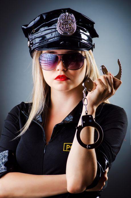 Junge blonde Frauen in Polizeiuniform trägt eine Sonnenbrille und hält Handschellen